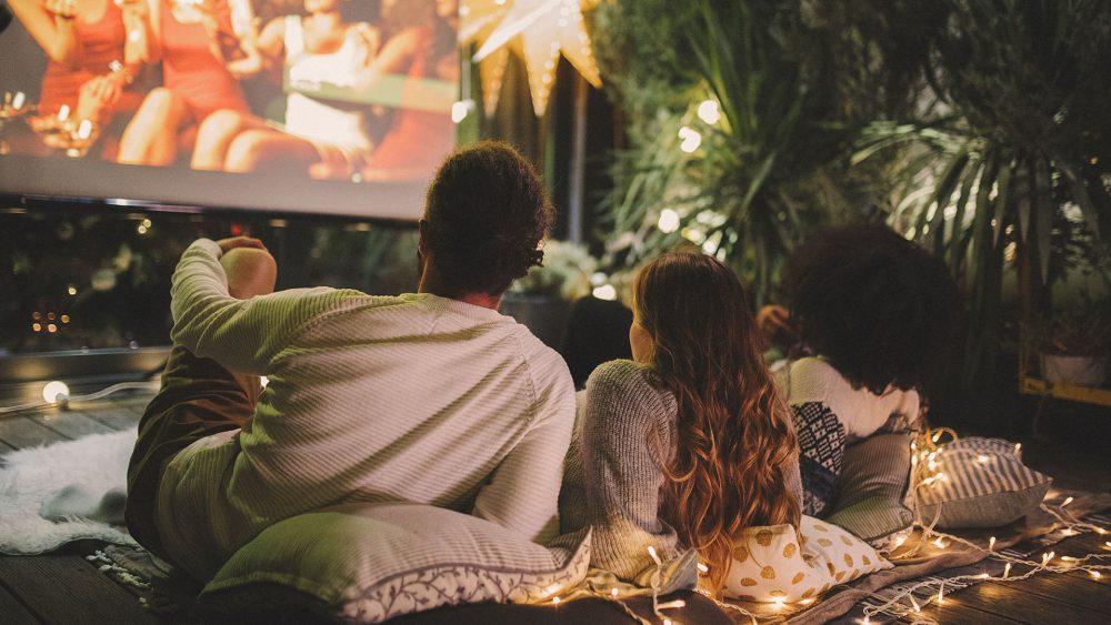Ein Paar liegt auf Kissen und Decken vor einer Leinwand und schaut einen Film im eigenen Garten.