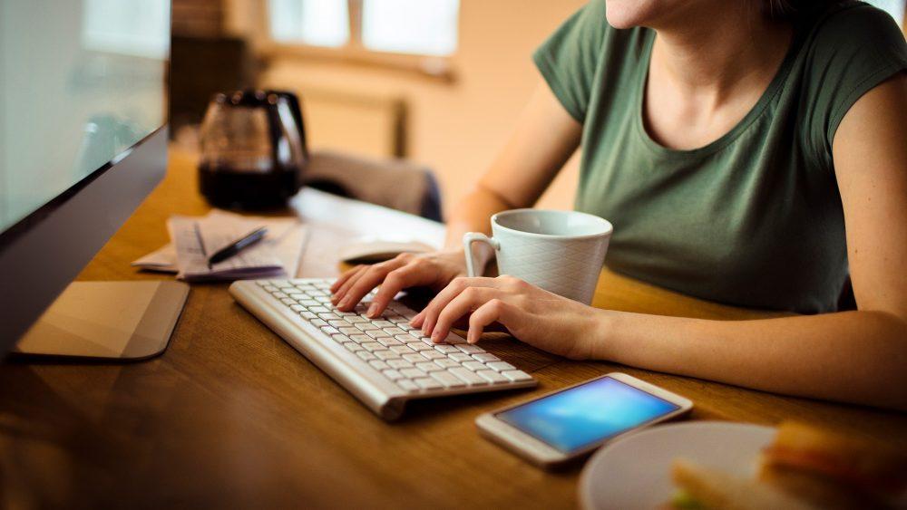 Eine Person sitzt vor einem Monitor und tippt auf einer Tastatur. Vor ihr liegt ein Smartphone.