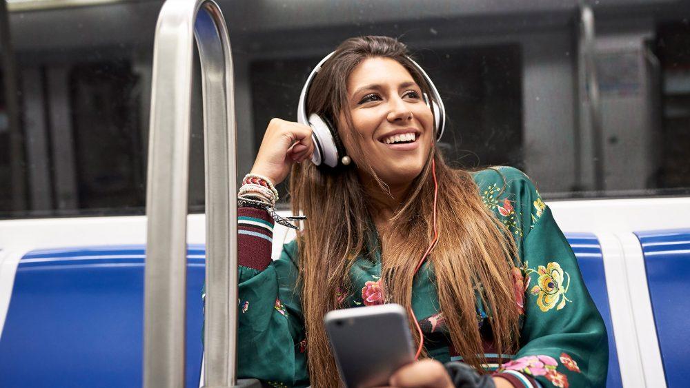 Eine Person fährt in der Bahn und hört dabei Musik von ihrem Smartphone.