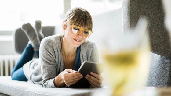 Eine Person liegt auf einem Sofa und schaut auf ein iPad.