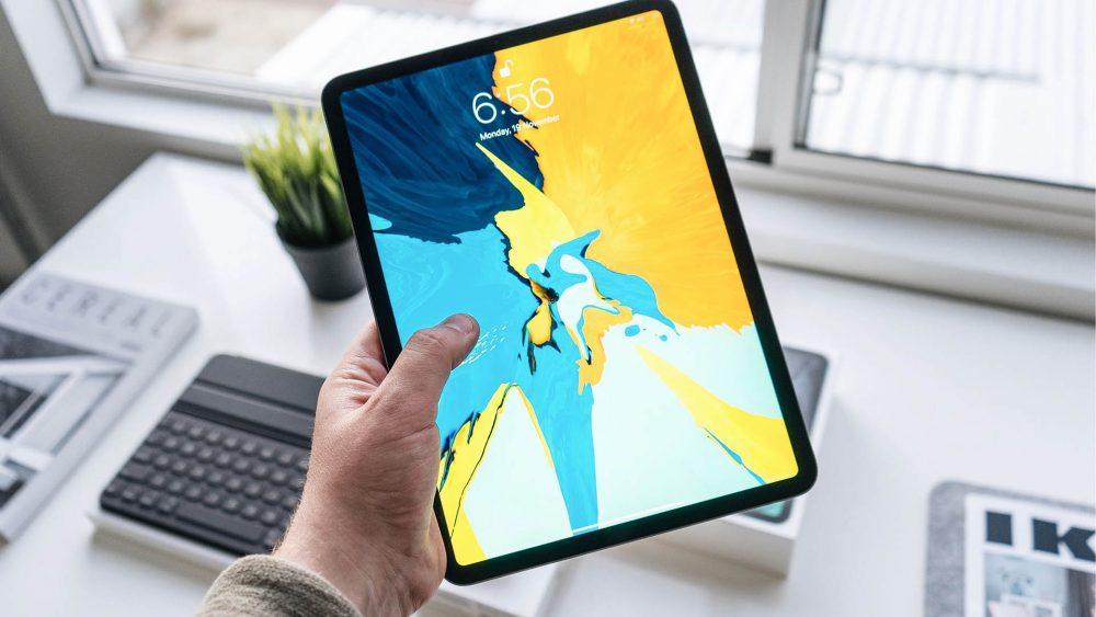 Eine Person hält ein iPad mit eingeschaltetem Display in die Kamera.