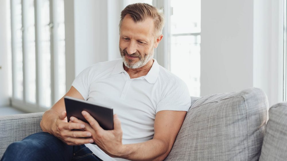 Eine Person sitzt auf einem Sofa und schaut auf ihr iPad.