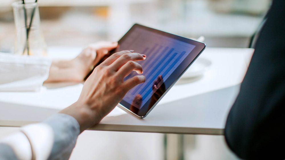 Eine Person hält ein iPad in der Hand. Darauf ist ein Balkendiagramm zu sehen.