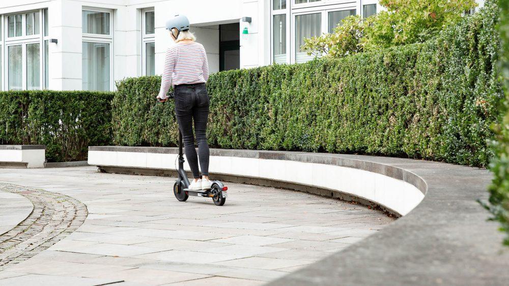 Eine Person fährt auf einem E-Scooter vor einer großen Hecke.