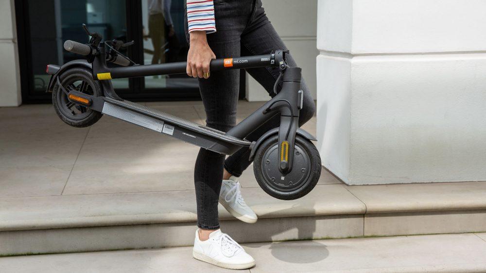 Eine Person läuft einige Stufen hinab. Dabei trägt sie einen zusammengeklappten E-Scooter in der Hand.