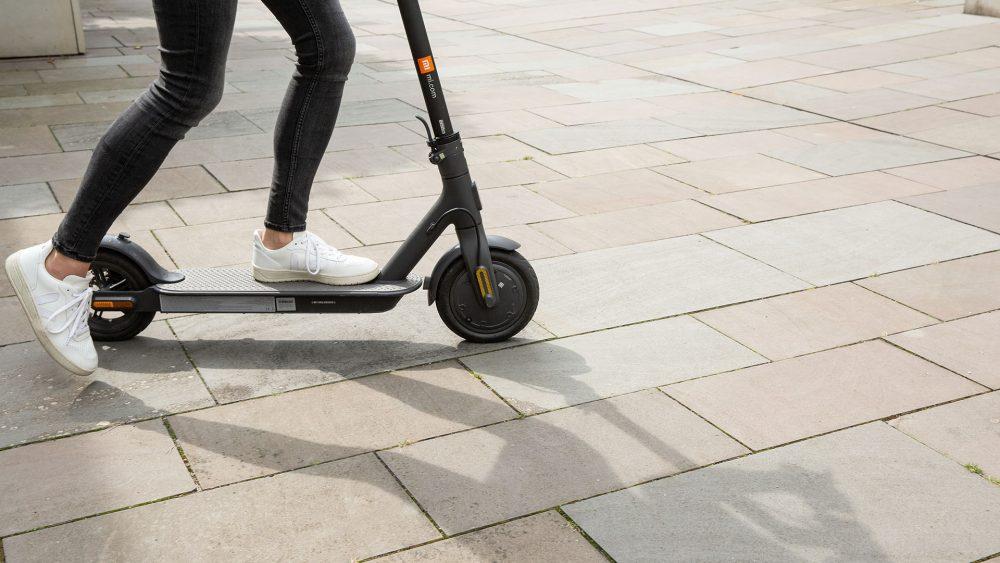 Eine Person steht auf einem E-Scooter. Zu sehen ist, wie sie mit dem Fuß Schwung holt, um den Roller zu starten.