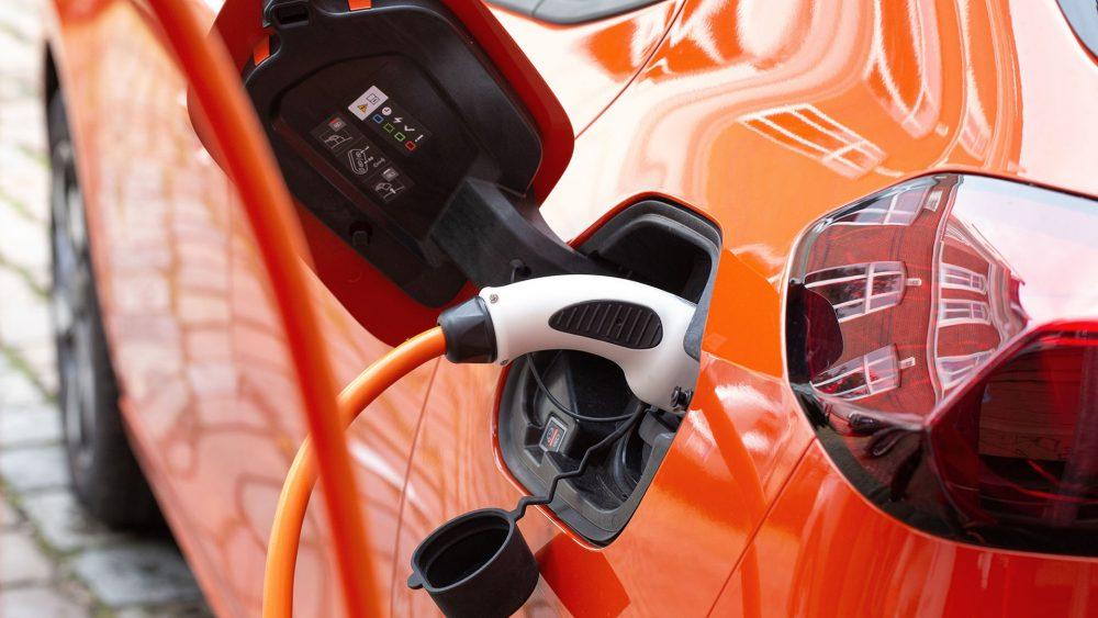 Ein Typ-2-Stecker steckt in einem orangen Opel Corsa-e.