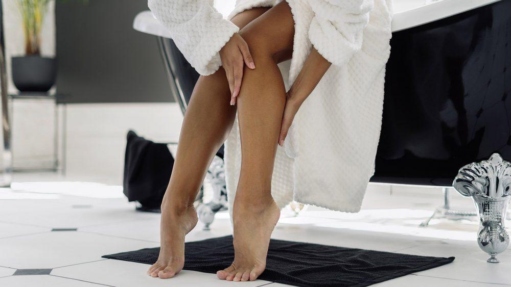 Eine mit einem Bademantel bekleidete Person sitzt auf dem Rand einer Badewanne. Sie streicht sich über die haarfreien Beine.