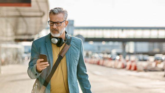 Eine Person blickt auf das Smartphone in ihrer Hand. Um den Hals trägt sie Kopfhörer.