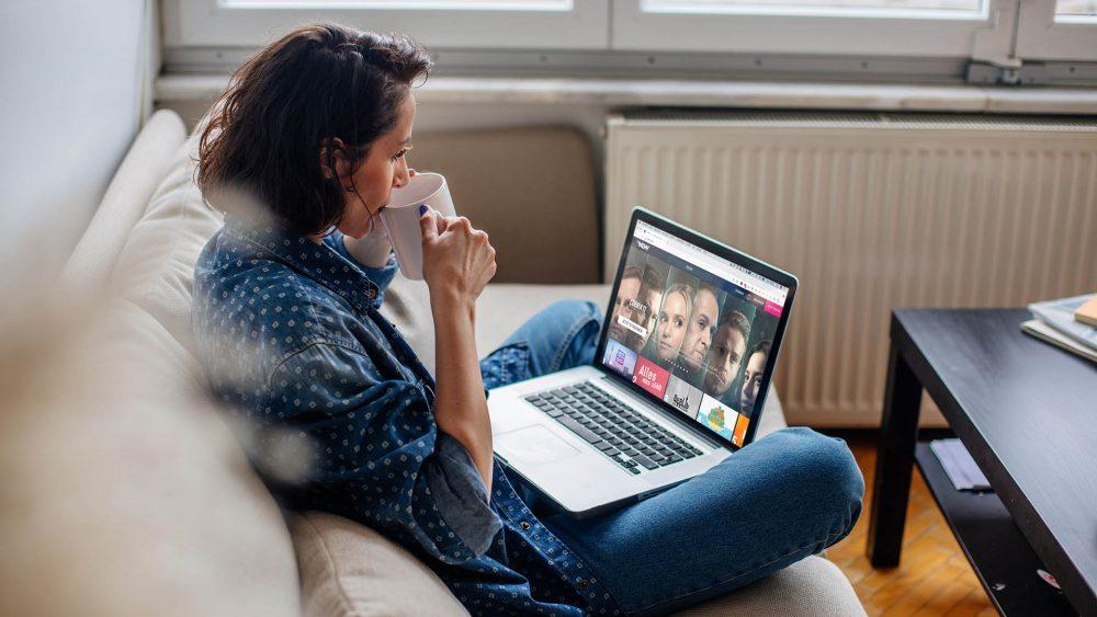 Eine Person sitzt mit einer Tasse in der Hand auf dem Sofa und schaut auf ihrem Laptop auf das Hauptmenü von TVNOW.