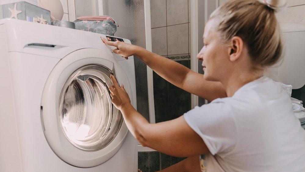 Eine Person sitzt vor einer Waschmaschine und bedient sie.