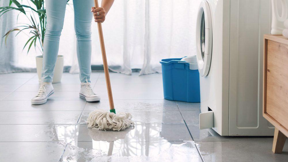 Eine Person wischt mit einem Mopp Wasser auf, das aus einer Waschmaschine gelaufen ist.