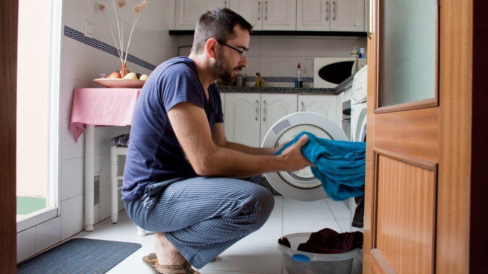 Eine Person holt ein Handtuch aus einer Waschmaschine.