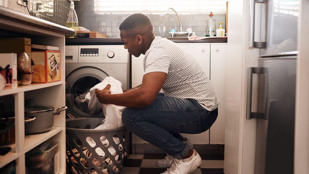 Eine Person holt Wäsche aus einer Waschmaschine.