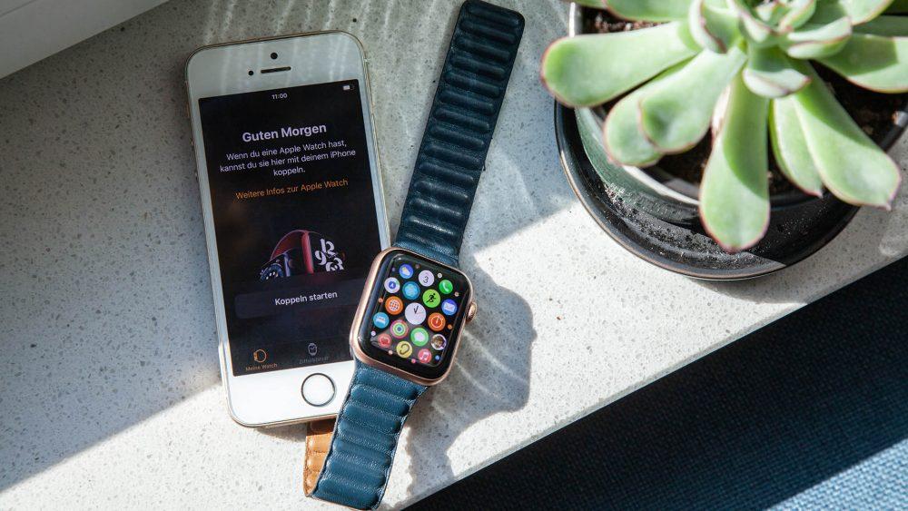Ein iPhone SE und eine Apple Watch SE liegen nebeneinander.