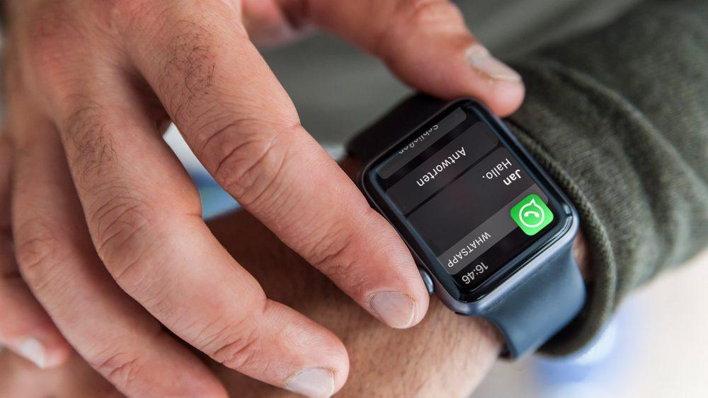 Eine Person trägt eine Apple Watch am Handgelenk. In der Nahaufnahme ist eine eingehende WhatsApp-Nachricht auf dem Display zu erkennen.