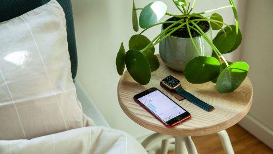 Eine Apple Watch und ein iPhone liegen nebeneinander auf einem Nachttisch.