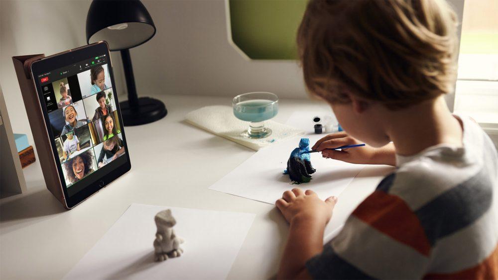 Ein Kind sitzt vor einem iPad, auf dem ein FaceTime-Call mit mehreren Teilnehmern läuft, und bemalt Figuren.