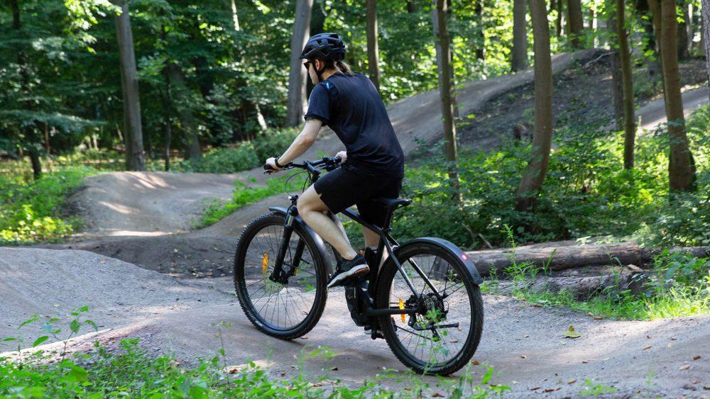 Eine Person fährt auf einem elektrischen Mountainbike über einen Bike-Trial.