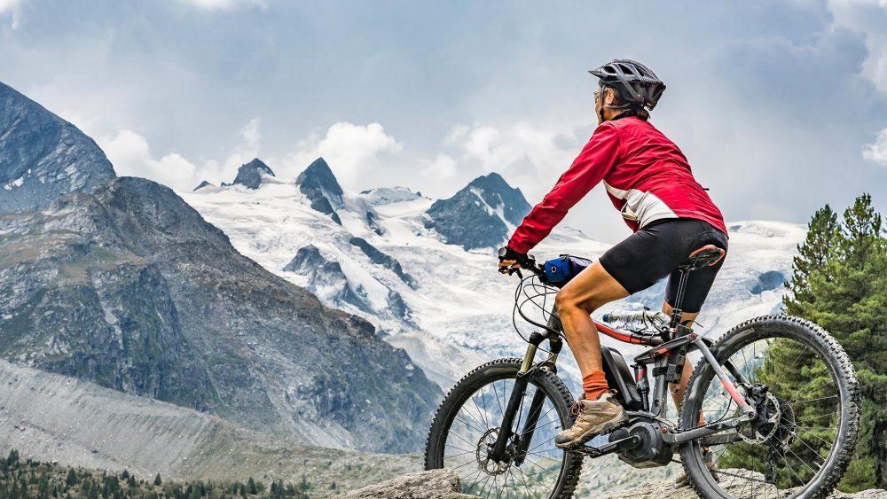 Eine Person sitzt auf einem Fully und schaut in Richtung großer Berge.