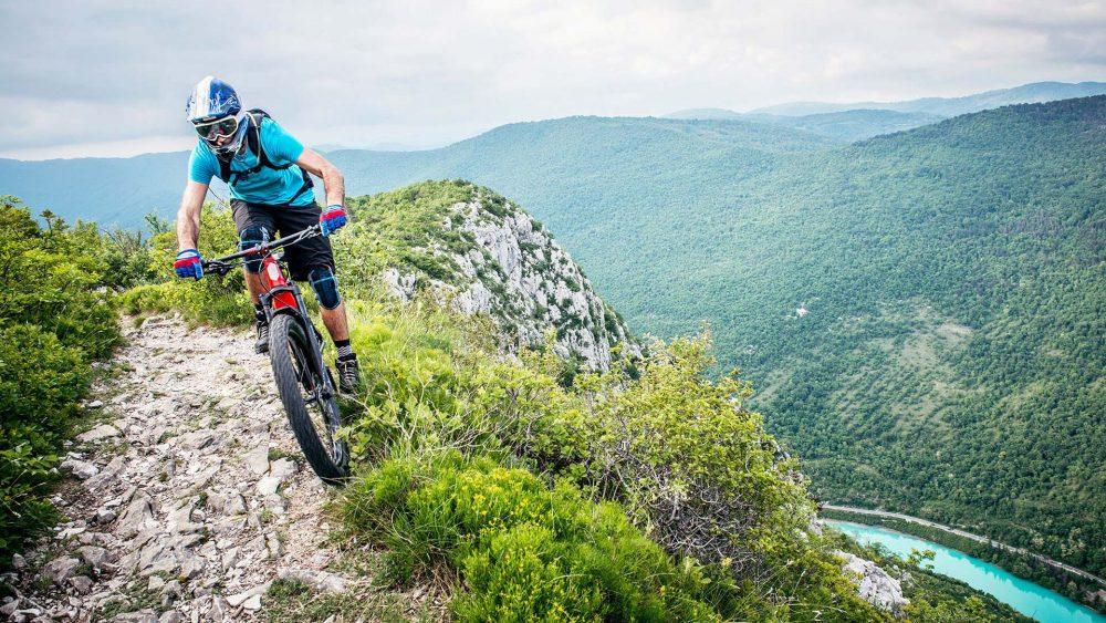 Eine Person fährt einen hohen Berg mit einem Mountainbike herunter.