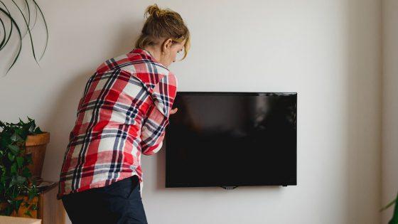 Eine Person montiert einen Flachbildfernseher an der Wand.