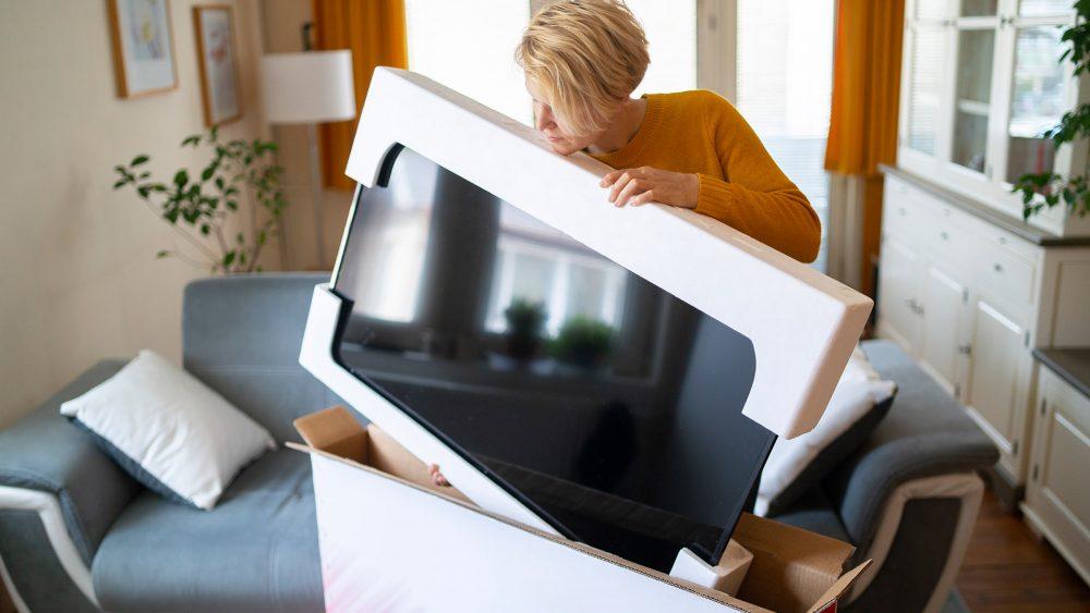Eine Person entnimmt einen neuen Fernseher aus der Originalverpackung.