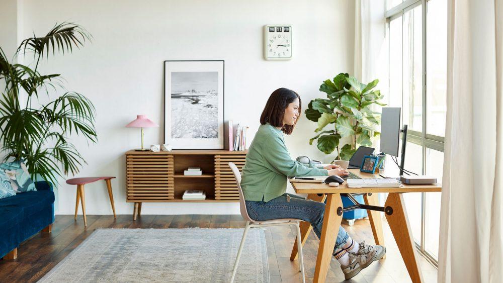 Eine Person sitzt an einem Schreibtisch. Ein Computer-Monitor ist mithilfe einer Tischhalterung daran befestigt.