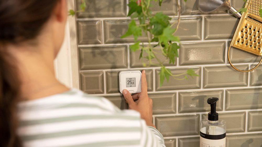 Eine Person bedient den Schalter FritzDECT 440, der an einer Wand angebracht ist.