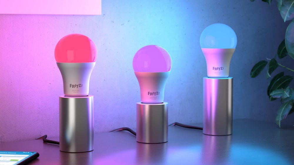 Drei Glühbirnen des Typs FritzDECT 500 nebeneinander leuchten in unterschiedlichen Farben.