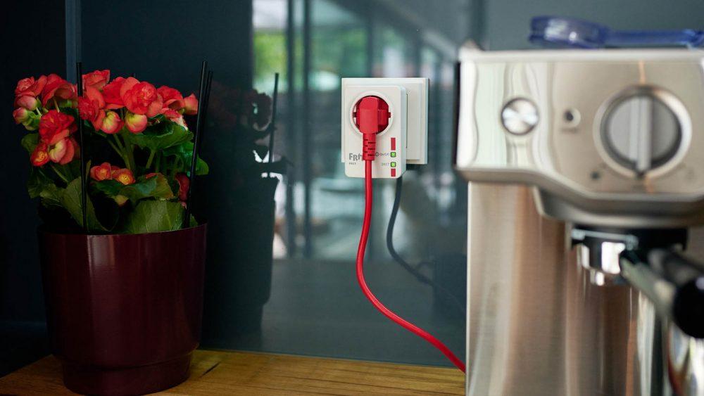 Ein FritzDECT Repeater 100 steckt in der Küche. Am Strom-Durchgang hängt eine Kaffeemaschine.