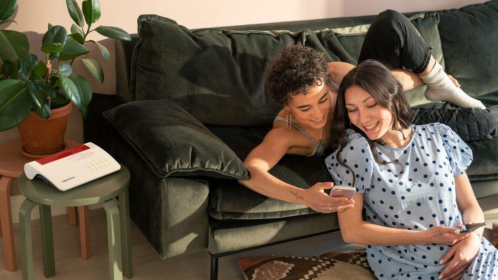 Zwei Personen sitzen in einem Wohnzimmer und schauen auf ein Smartphone. Neben ihnen steht eine Fritzbox 7590 AX auf einem kleinen Tisch.