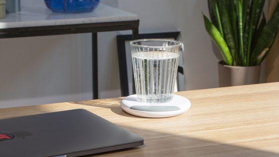 Auf einem Büroschreibtisch steht ein Wasserglas auf dem Beurer Trinkmanager.
