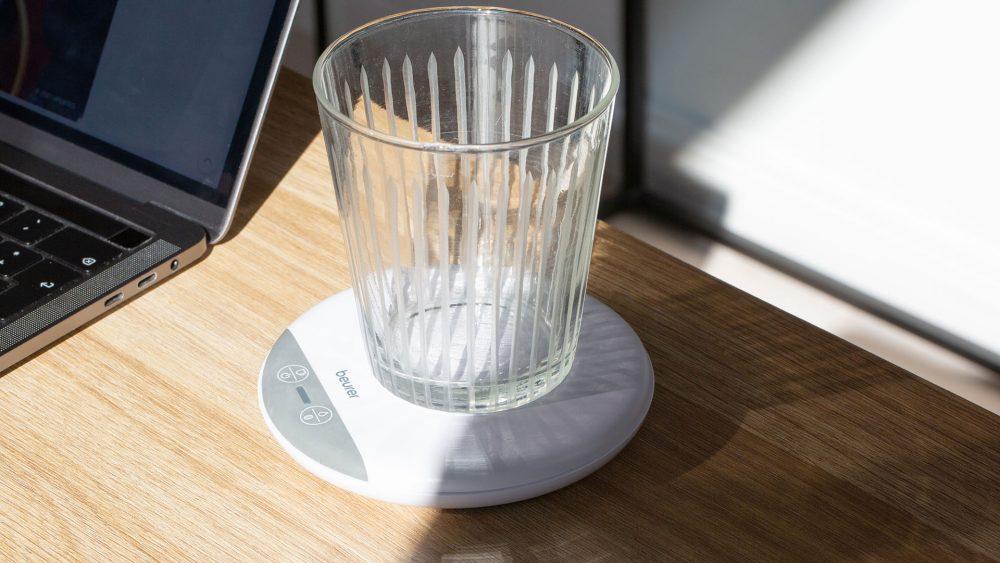 Auf einem Schreibtisch steht der Beurer Trinkmanager mit einem leeren Glas.