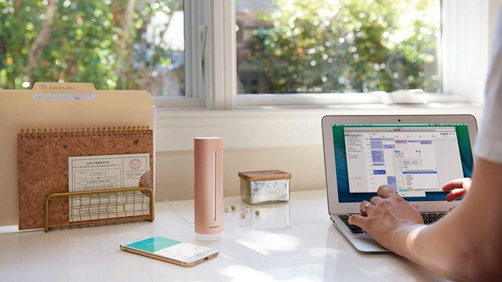 Auf einem Schreibtisch im Homeoffice steht der Netatmo Raumluftsensor. Eine Person sitzt am Schreibtisch und arbeitet an einem Laptop.