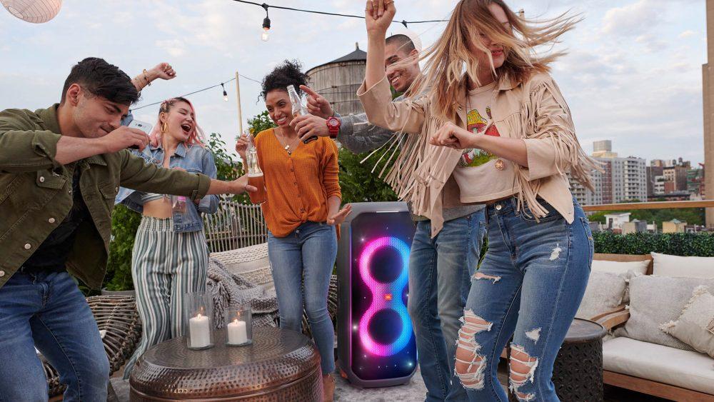Mehrere Leute tanzen vor einer JBL PartyBox 710.
