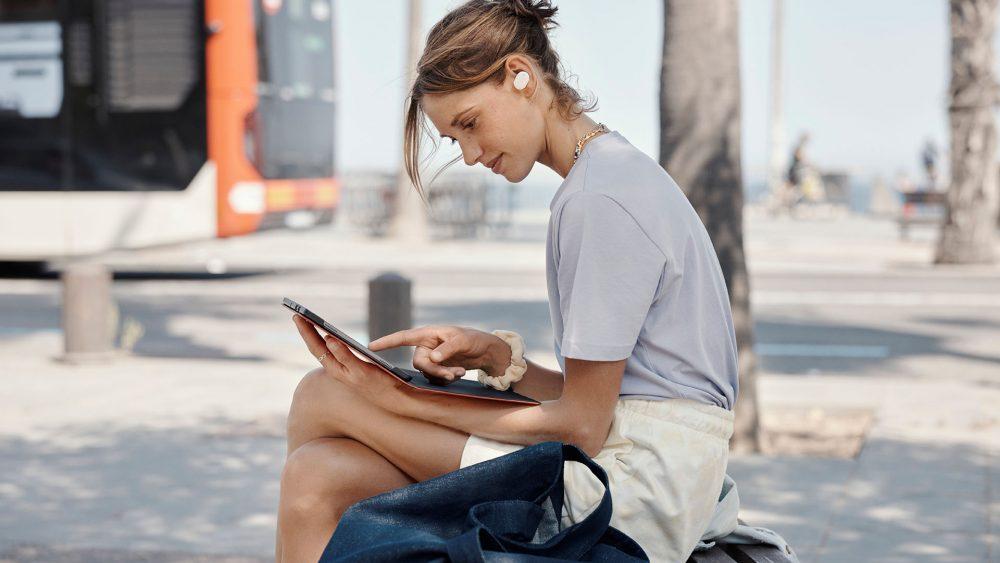 Eine Person sitzt auf einer Bank und bedient ein Tablet. Im Ohr hat sie die JBL Tune 130NC.