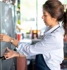 Eine Person untersucht die Tür eines Kühlschranks genau.