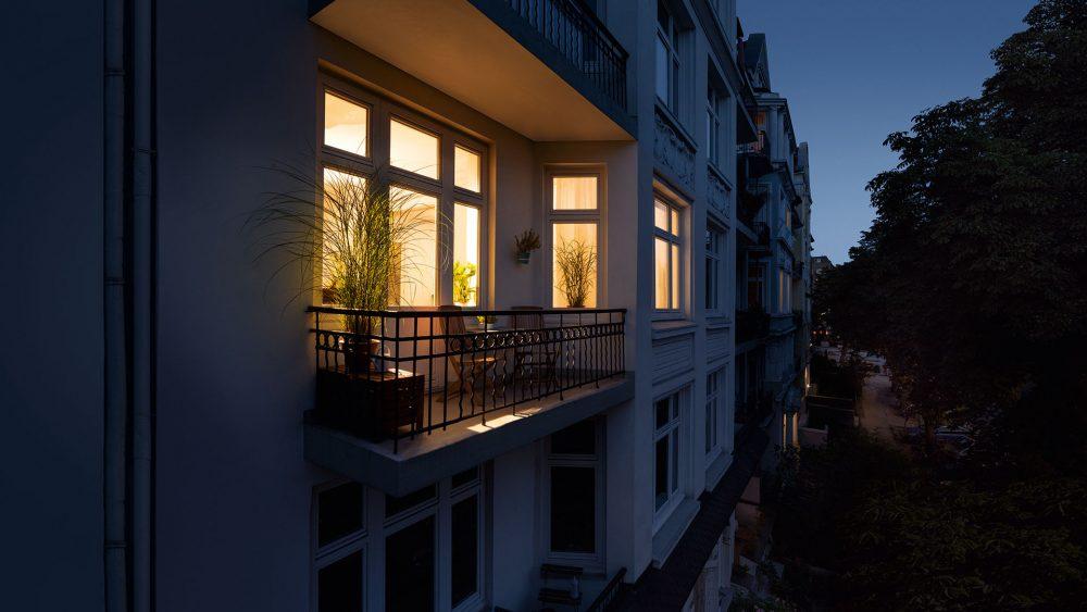 Blick auf einen Balkon. In der Wohnung im Hintergrund brennt Licht.