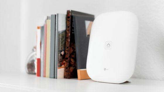 Eine Telekom Magenta Smarthome Home Base steht auf einem Regal neben Büchern.
