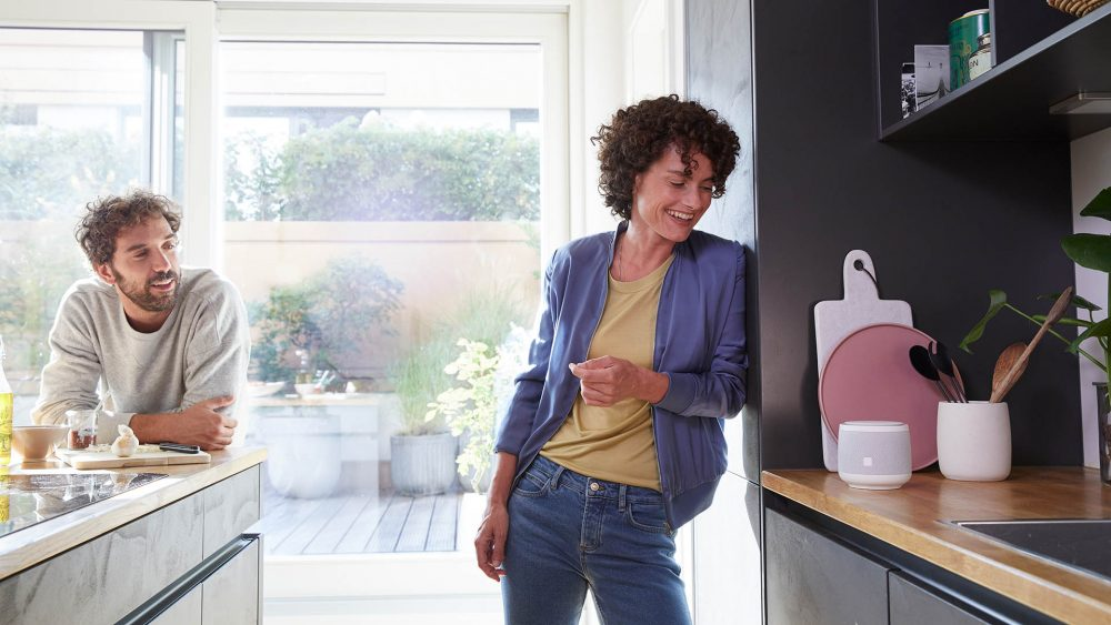Zwei Personen stehen in einer Küche. Auf der Arbeitsplatte ist ein smarter Lautsprecher der Telekom zu sehen.