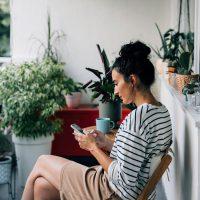 Eine Person sitzt auf einem Balkon und hält ein Smartphone in der Hand.