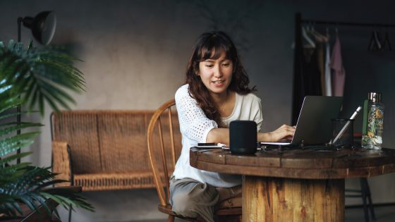Eine Person sitzt an einem Tisch, vor ihr steht ein aufgeklappter Laptop. Sie spricht zu einem smarten Lautsprecher.