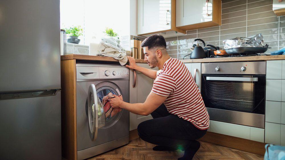 Eine Person bestückt die Waschmaschine mit Wäsche.
