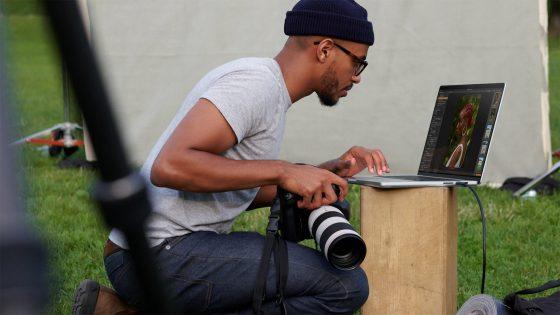 Eine Person mit einer Kamera in der Hand betrachtet die geschossenen Bilder auf einem MacBook Pro.