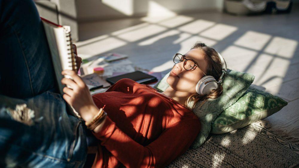 Eine Person liegt auf dem Boden, liest etwas und hört dabei Musik über Kopfhörer.