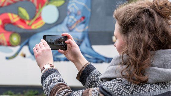 Eine Person hält ein Smartphone in den Händen, um ein Foto zu machen.