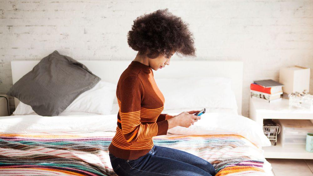 Eine Person sitzt auf dem Bett und hält ein Smartphone in den Händen.