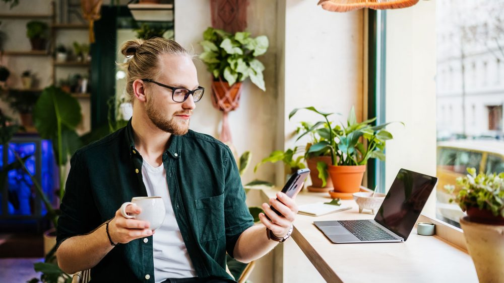 Eine Person sitzt an einem Laptop und schaut auf ein Smartphone, das sie in der Hand hält.