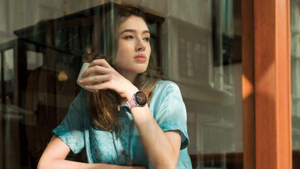 Eine Person sitzt in einem Café und schaut aus dem Fenster. An ihrem Handgelenk ist eine Huawei Watch GT 3 zu sehen.